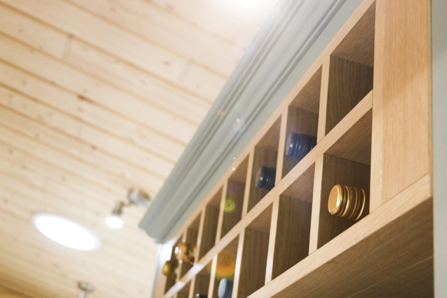 Spacious wine rack built into the cabinet above the fridge. Bespoke kitchen, customer case study in a log cabin the Staffordshire countryside. Handmade by Mudd & Co