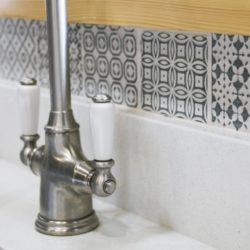 The elegant Perrin & Rowe tap and delicate green patterned tiles sit beautifully together. Bespoke kitchen, customer case study in a log cabin the Staffordshire countryside. Handmade by Mudd & Co