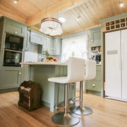 Wide shot showing how the kitchen sits in the open-plan living space. Bespoke kitchen, customer case study in a log cabin the Staffordshire countryside. Handmade by Mudd & Co
