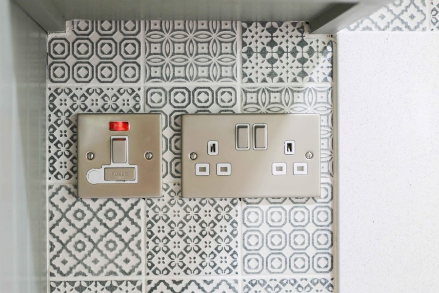 Close up image of tiles around wall sockets. Bespoke kitchen created for our customer who lives in a log cabin the Staffordshire countryside. Handmade by Mudd & Co