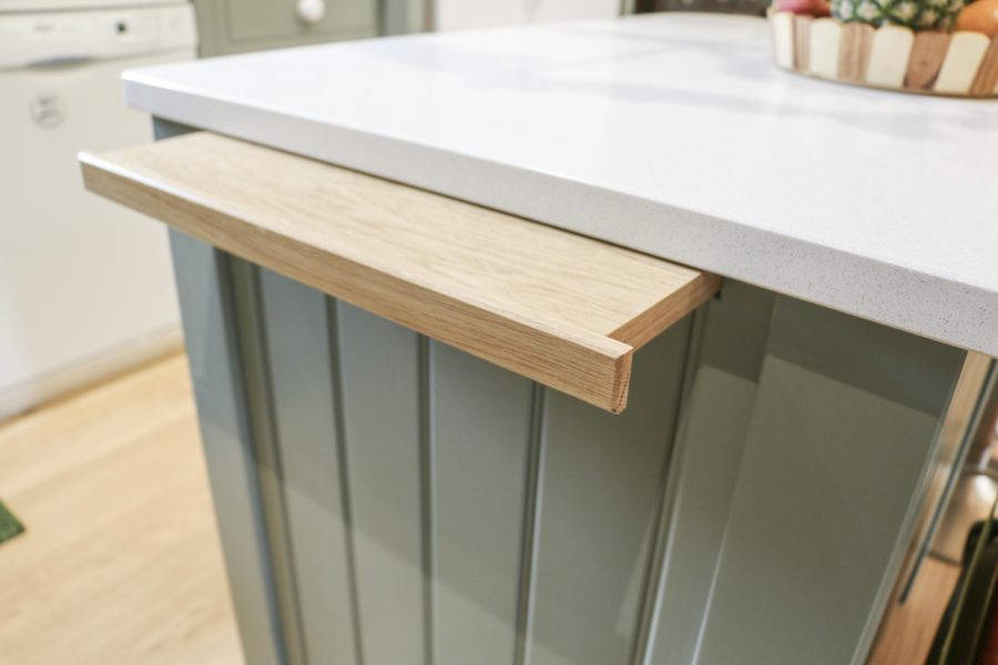 Retractable wooden shelf built into the kitchen, opposite the oven. Bespoke kitchen created for our customer who lives in a log cabin the Staffordshire countryside. Handmade by Mudd & Co