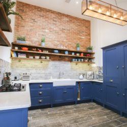 This contemporary, deep blue kitchen can be found in Leek, Staffordshire. The property is a renovated country townhouse, with an impressive double height space for their kitchen-diner. Bespoke kitchen, traditionally handcrafted by Mudd & Co