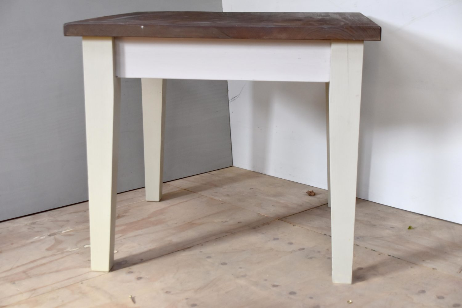 This four foot tapered leg table is hand painted in Farrow & Ball Cornforth White with a stained table top. Hand crafted by Mudd & Co.