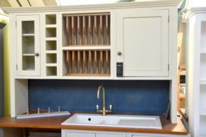 This kitchen wall unit rack cleaner's is hand painted cream and has cupboards, a plate rack, a wine rack and a glazed unit. Hand crafted by Mudd & Co.