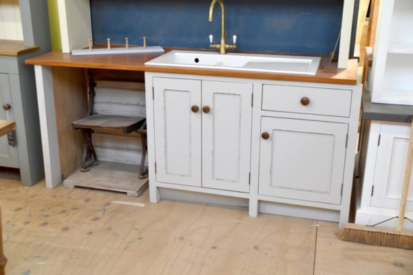 This kitchen sink unit is painted in light grey with a distressed finish. The unit includes a Villeroy & Boch ceramic sink, mahogany worktop and space for a freestanding dishwasher. Hand crafted by Mudd & Co.